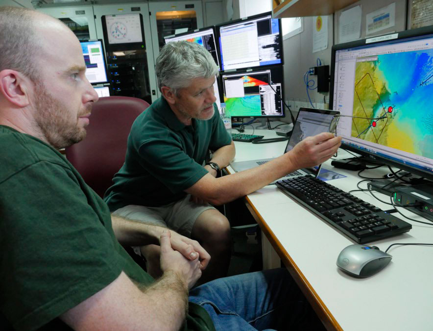 Two people working on a computer in the operations room on RV Investigator.