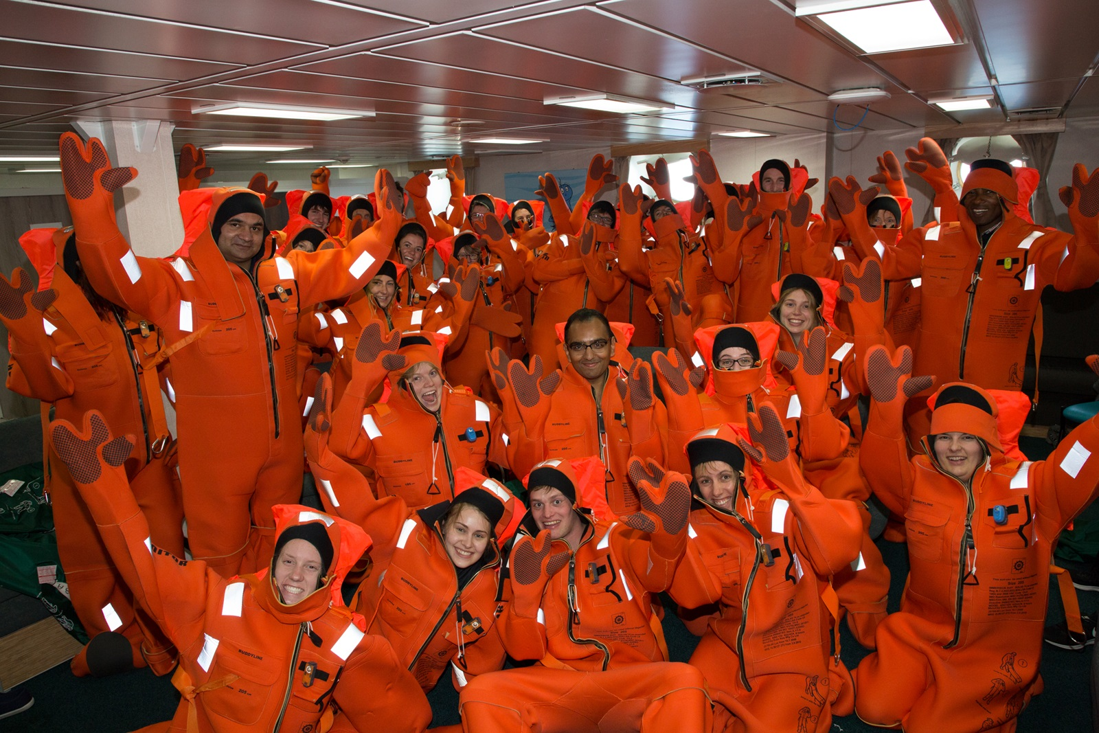 A large group of people in colourful immersion suits raise their arms into the air.