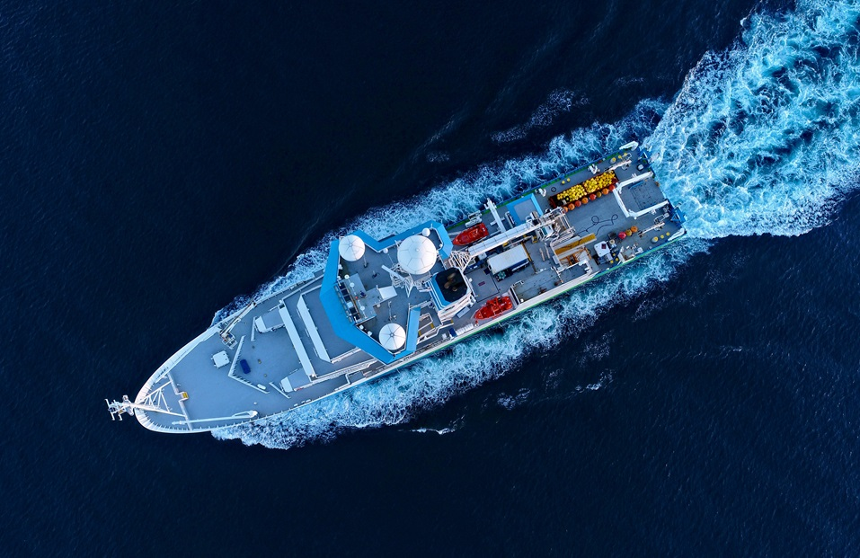 Aerial shot from directly overhead of a ship on the ocean.