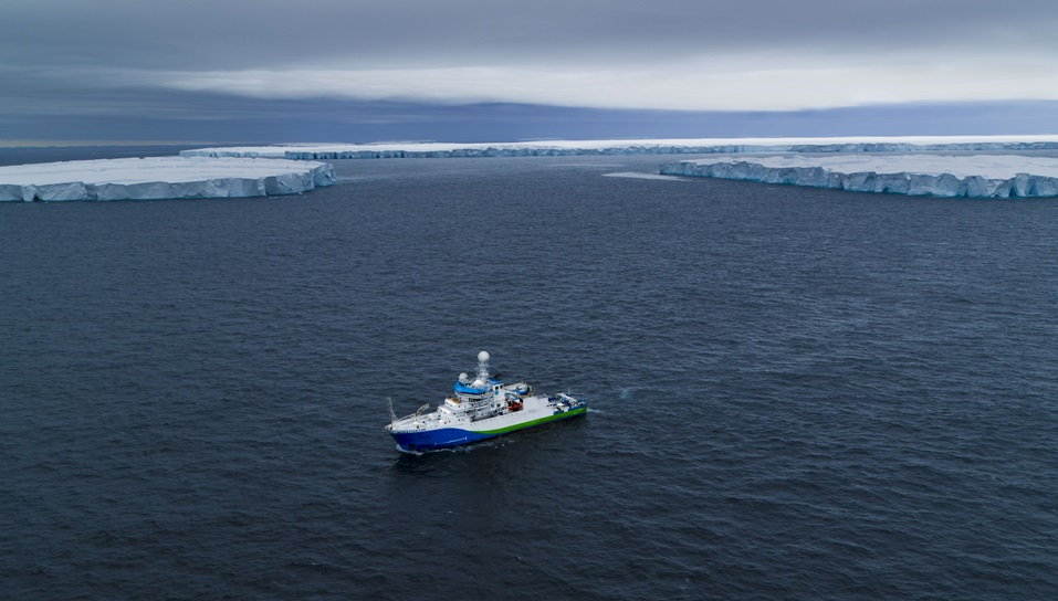 A ship photographed from above with icebergs in the background.