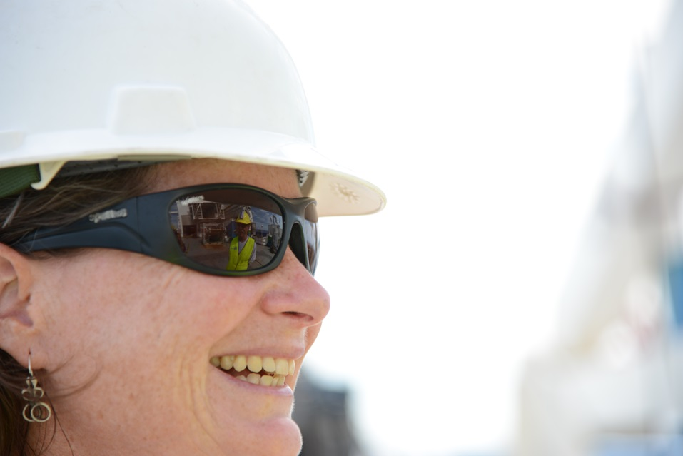 A close up of a woman in a hard hat smiling off camera.