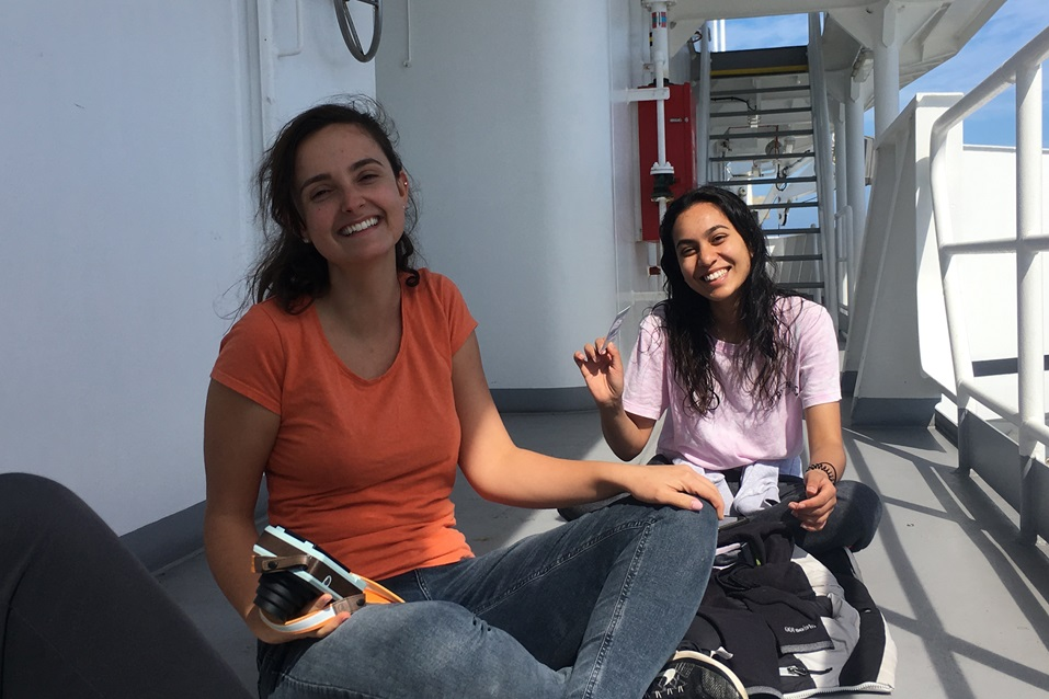 Two women sit on the deck of a ship and smiling.