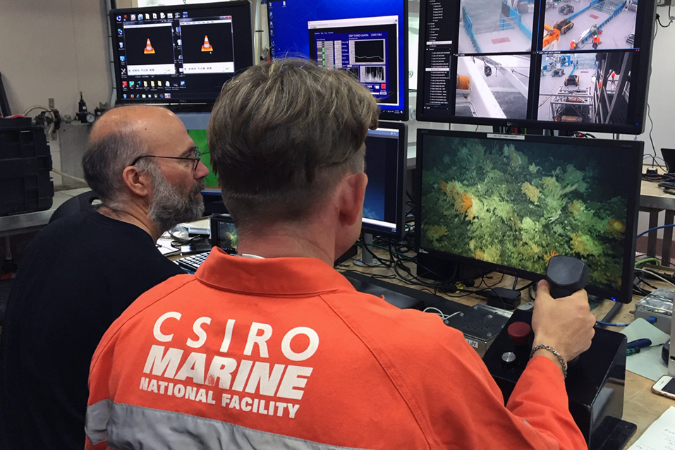 A man in an orange work suit with CSIRO Marine National Facility written on the back holds a joystick and stares at a screen showing an underwater image.