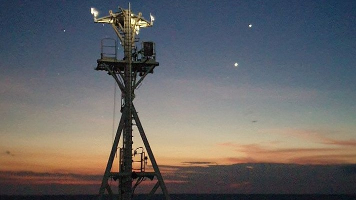View at sunset of ship mast with lights and various scientific instruments on it and two bright stars in the sky behind.