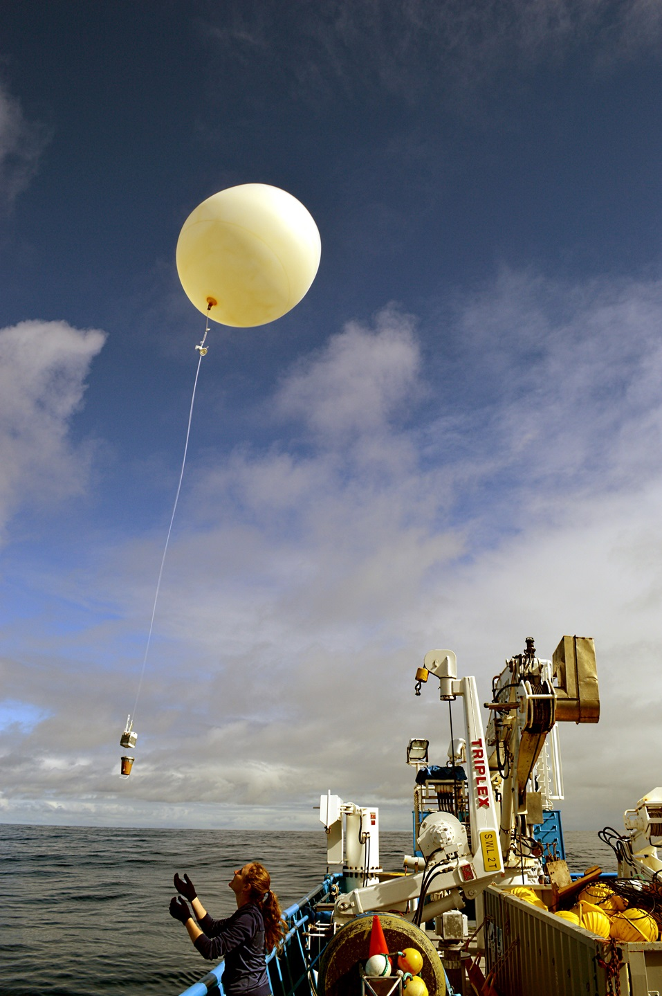A women lets go of a weather balloon from on the deck.