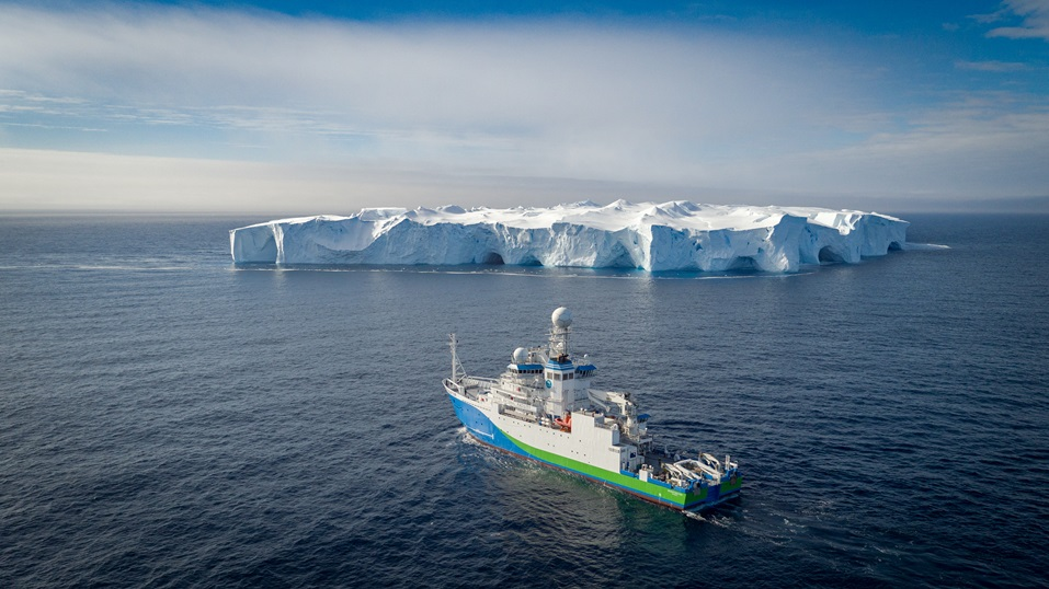 RV Investigator at sea with a mega-ice berg in the background.