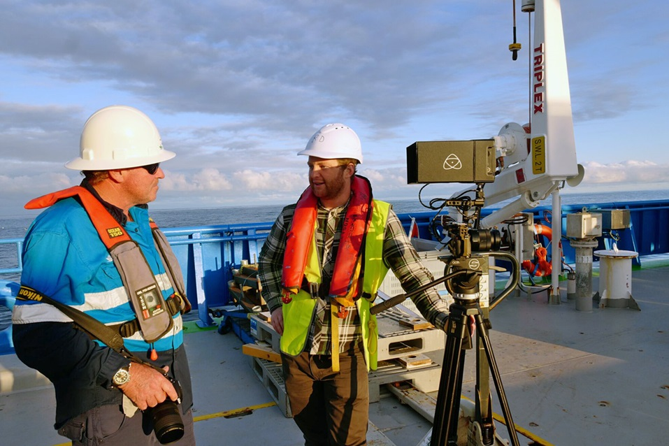 Two people on deck with apiece of equipment that looks like a camera on a tripod.