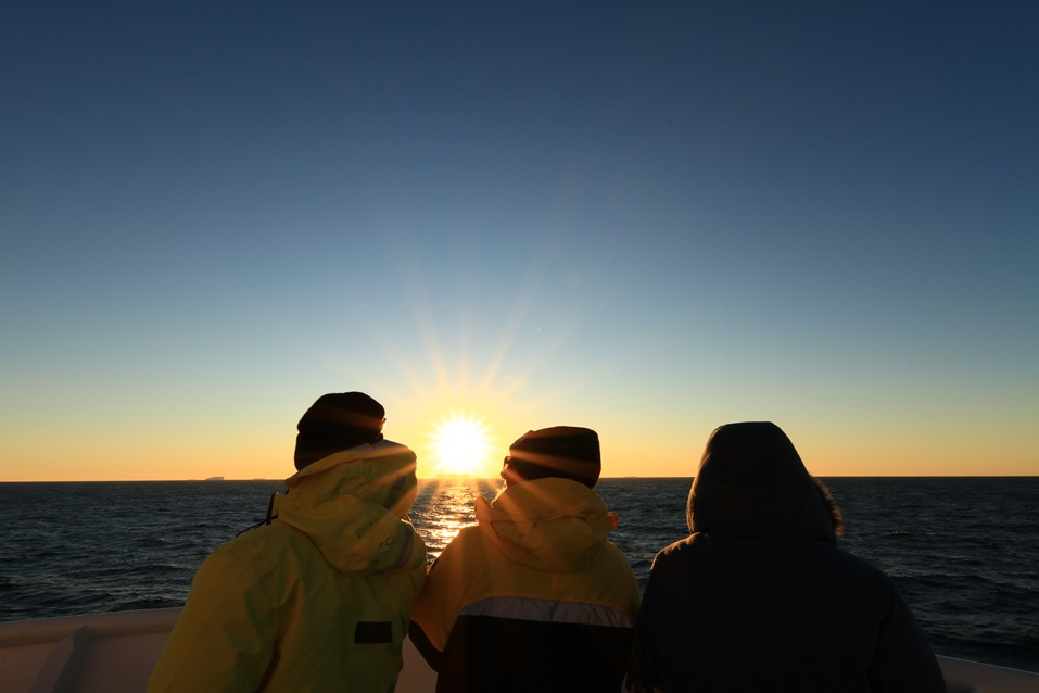 Three scientists watch a sunset in Antarctica.