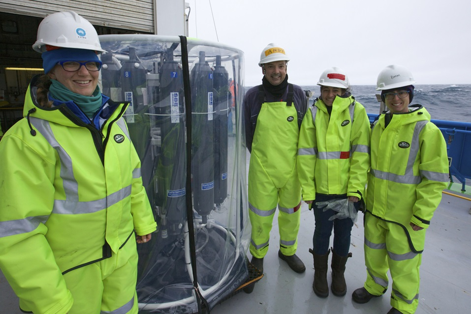 Four scientists in cold weather gear stand on the deck of a ship next to a large circular scientific instrument.