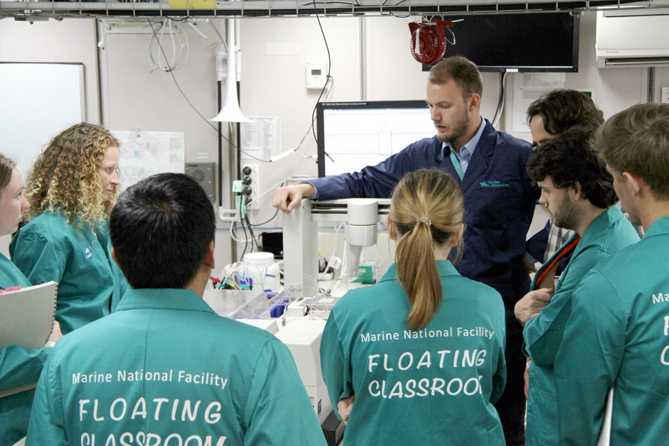 A group of students in lab coats listen to a scientist in a laboratory on a vessel.